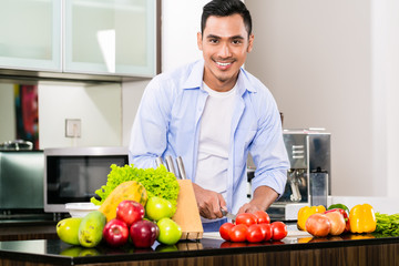 Asian man cutting salad in kitchen