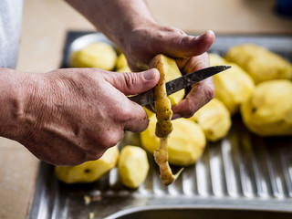 Hands peeling potatoes