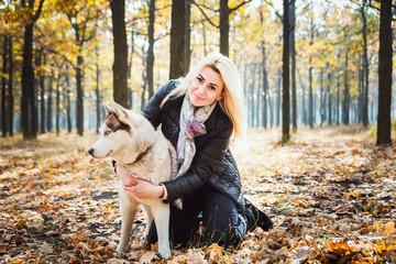 young beautiful female having fun with siberian husky in autumn park