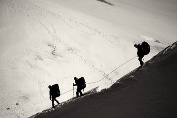 Three mountaineers walking across Mont Blanc high mountain range