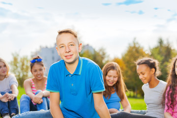 International teenagers sitting together in park
