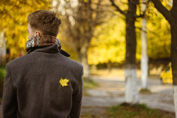 beautiful happy stylish man in a coat with little yellow leaf on
