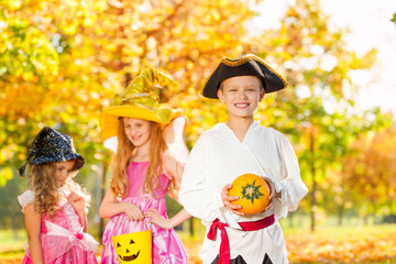 Friends in Halloween costumes hold small pumpkin