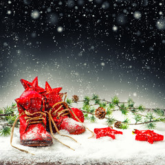 Christmas decoration with antique baby shoes. Falling snow