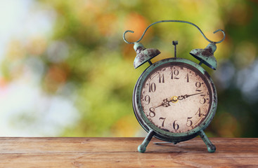 image of vintage alarm clock on wooden table in front of abstract blurred background. retro filtered