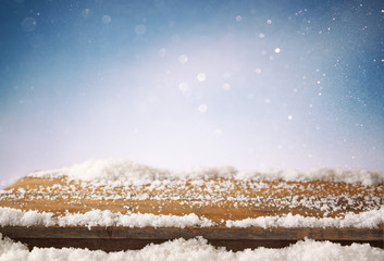 image of wooden old table and december fresh snow on top. in front of glitter background. selective focus