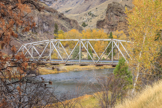 A steel bridge spans the Bitterroot river in western Montana during Autumn.