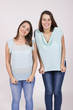 Two lookalike sisters, cute and intimate portrait in studio