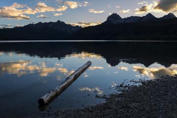 Log in lake at sunset.