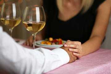Elegant couple holding hands in the restaurant