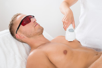 Beautician Giving Laser Epilation On Man's Chest
