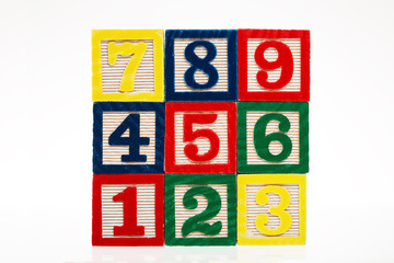 Colorful stacked toy plastic building blocks with numbers isolat