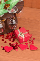 glass of vine, red hearts and small present