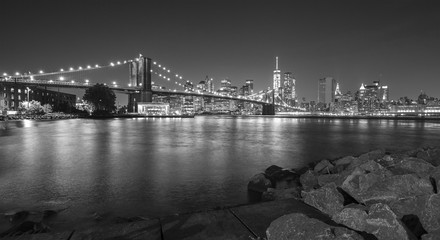 Black and white photo of Manhattan waterfront at night, NYC, USA