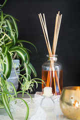 Aroma reed diffuser, candle, lace and spider plant against blackboard wall. Selective focus on thebottle and sticks.