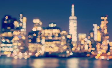 Vintage toned blurred Manhattan waterfront at night, NYC, USA.