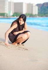 Biracial teen girl on Waikiki beach drawing in the sand