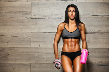 Strong fitness girl with cocktail bottle after workout in gym.