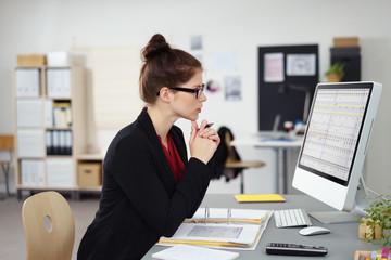 angestellte im büro schaut auf kalkulation am pc