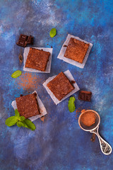 Homemade chocolate brownies with hazelnuts on grunge blue wooden background. Top view. Space for text
