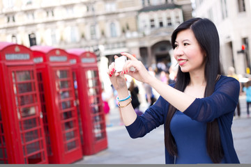 Japanese woman in London taking a photo with her phone