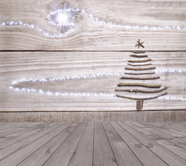 Christmas tree arranged from sticks on empty wooden deck table on sparkly grey background. Ready for product display montage.