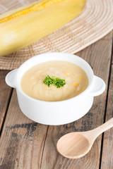Corn cream soup in white bowl.
