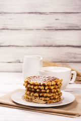 Stack of thick belgium waffles with sugar powder and cup of cappuccino coffee. Tasty breakfast concept. Selective focus