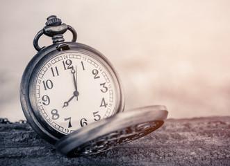 vintage pocket watch on blurred background