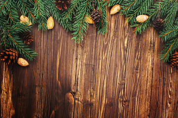 Christmas wooden background with fir tree branches, cones and nuts. Toned image. Retro style