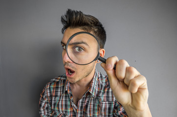 Funny image of a handsome man playing with a magnifying glass on a grey background - caucasian people - people concept