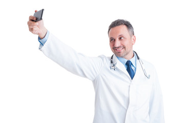 Handsome doctor or medic taking a selfie with smartphone