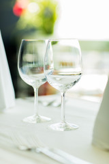 close up of two wine glasses on restaurant table