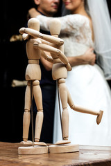Wooden people staying and hugging, wedding couple  at bokeh. People relationship concept