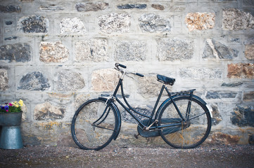 Old rusting bicycle leaning against a stone wall