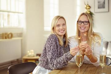 frauen feiern zuhause mit wunderkerzen