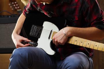 Young man playing electric guitar.