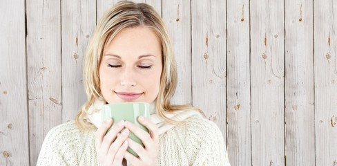 Composite image of happy woman enjoying a hot coffee standing