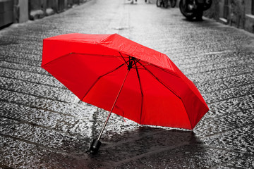 Fototapete - Red umbrella on cobblestone street in the old town. Wind and rain