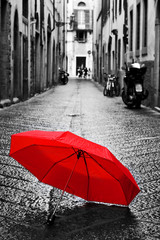 Wall Mural - Red umbrella on cobblestone street in the old town. Wind and rain