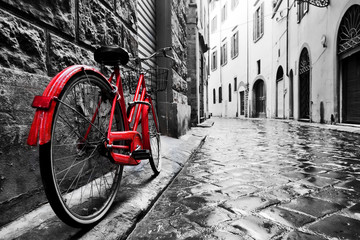 Poster Bicycle Retro vintage red bike on cobblestone street in the old town. Color in black and white