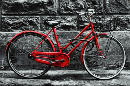 Fototapete Retro vintage red bike on black and white wall.