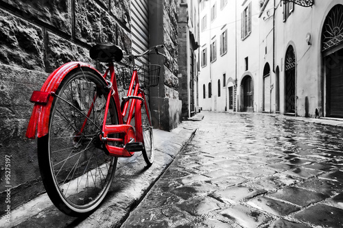 Fototapete Retro vintage red bike on cobblestone street in the old town. Color in black and white