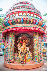 Durga Puja pandal and idols being worshipped with flowers.