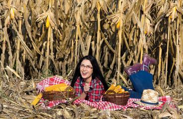 Farmer girl lying in corn field