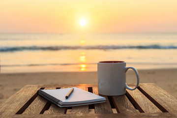 Coffee cup on wood table at sunset or sunrise beach