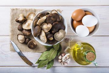 Pleorotus eryngii o setas de cardo con ingredientes para cocinar en la mesa de la cocina
