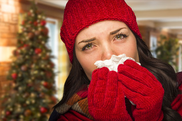 Sick Woman Blowing Her Nose With Tissue In Christmas Setting