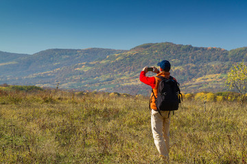 Male tourist with backpack taking pictures of  scenery to your s