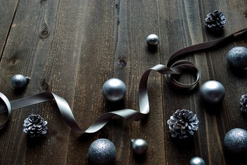 Silver Christmas ornaments with ribbon on black wooden background